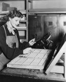 Mulher que trabalha na loja de impressão (todas as pessoas descritas não são umas vivas mais longo e nenhuma propriedade existe G Fotografia de Stock Royalty Free