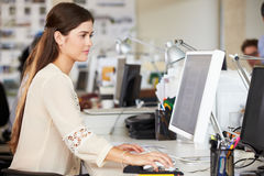 Mulher que trabalha na mesa no escritório criativo ocupado Imagem de Stock Royalty Free