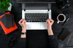 Mulher que trabalha na tabela do escritório Vista superior das mãos humanas, do teclado do portátil, de uma xícara de café, do sm Imagem de Stock