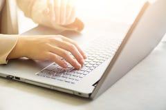 Mulher que trabalha no fim do computador acima A mulher entrega a datilografia no teclado do portátil, detalhe em linha da compra imagem de stock