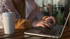 Mulher que trabalha no portátil com uma xícara de café filme