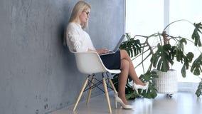 Mulher que trabalha no portátil no escritório vídeos de arquivo