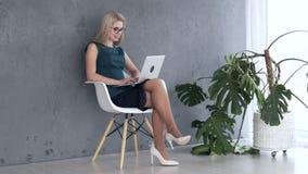 Mulher que trabalha no portátil no escritório filme