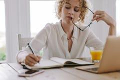 Mulher que trabalha no portátil que senta-se em casa foto de stock royalty free