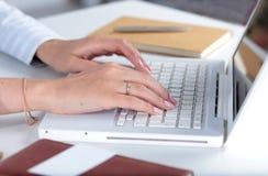Mulher que trabalha no portátil, sentando-se na mesa Fotografia de Stock Royalty Free