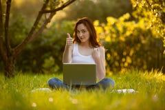 Mulher que trabalha no portátil que stiiting na grama verde Fotografia de Stock Royalty Free