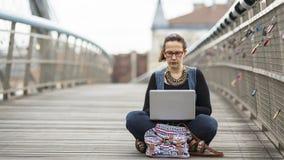 mulher que trabalha no portátil ao sentar-se na rua O conceito do Freelancer ou do Blogger de trabalho Imagens de Stock