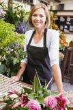 Mulher que trabalha no sorriso da loja de flor Fotos de Stock Royalty Free