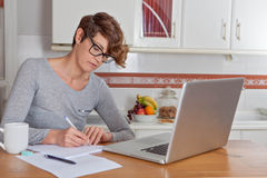 Mulher que trabalha ou que blogging no escritório domiciliário