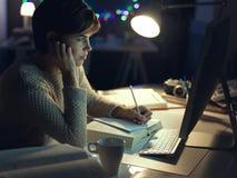 Mulher que trabalha tarde na noite imagens de stock