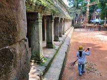 Mulher que trabalham perto do templo de Ta Prohm, e terreno de construção para o MAI fotografia de stock royalty free