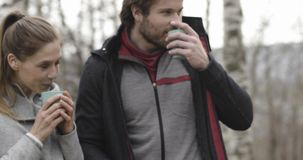 Mulher que traz a bebida ou café ou chá quente para equipar no lugar de acampamento Acople povos na viagem exterior do outono do  filme