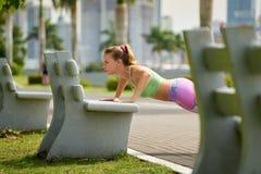 Mulher que treina Pectorals que faz flexões de braço na rua Bench-3 imagens de stock
