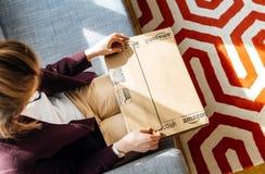 Mulher que unboxing desembalando Amazonas COM encaixota Foto de Stock Royalty Free