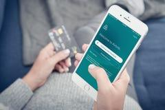 Mulher que usa Airbnb app no iPhone 8 de Apple positivo Imagem de Stock Royalty Free