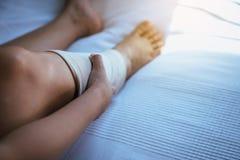 Mulher que usa a atadura elástica sobre posta com os pés que têm a dor do joelho ou de pé imagem de stock