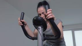 Mulher que usa a bicicleta de exercício filme