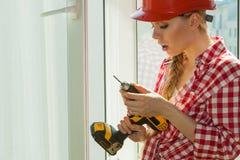 Mulher que usa a broca na janela foto de stock