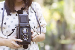 Mulher que usa a câmera do vintage que toma fotos Imagem de Stock Royalty Free