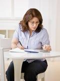 Mulher que usa a calculadora às contas de pagamento Imagem de Stock