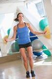 Mulher que usa a corda de salto na ginástica Fotos de Stock