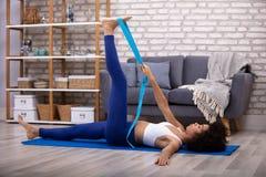 Mulher que usa a correia da ioga ao fazer o exerc?cio imagens de stock royalty free