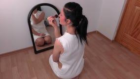 Mulher que usa a escova da composição perto do espelho filme