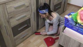 Mulher que usa a escova no assoalho na sala video estoque