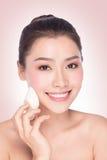Mulher que usa a esponja cosmética na face com sorriso Imagens de Stock