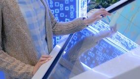 Mulher que usa a exposição do écran sensível dos multimédios do quiosque interativo filme