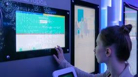 Mulher que usa a exposição interativa do écran sensível na exposição moderna da tecnologia foto de stock