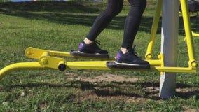 Mulher que usa a máquina deslizante do treinamento no parque filme