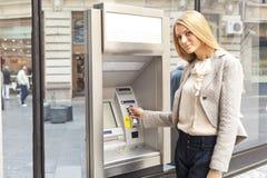 Mulher que usa a máquina do ATM do banco fotos de stock royalty free