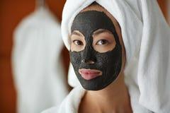 Mulher que usa a máscara protetora da limpeza da pele fotos de stock