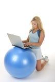 Mulher que usa a mesa da esfera do exercício Fotos de Stock