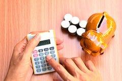 A mulher que usa moedas da calculadora e do mealheiro e da pilha pôs ao lado Fotos de Stock