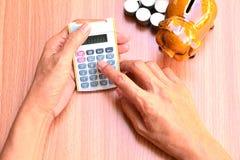 A mulher que usa moedas da calculadora e do mealheiro e da pilha pôs ao lado Imagem de Stock