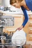 Mulher que usa a máquina de lavar louça Foto de Stock Royalty Free