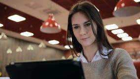 Mulher que usa o écran sensível do tablet pc no café filme
