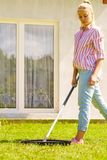 Mulher que usa o ancinho para limpar o jardim Fotografia de Stock Royalty Free