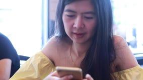 Mulher que usa o app no smartphone vídeos de arquivo