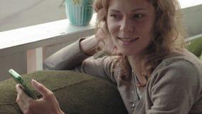 Mulher que usa o app no smartphone no café que sorri e que texting no telefone celular Fêmea ocasional nova multicultural bonita video estoque