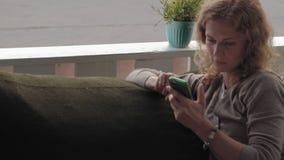 Mulher que usa o app no smartphone no café que sorri e que texting no telefone celular Fêmea ocasional nova multicultural bonita vídeos de arquivo