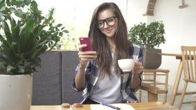 Mulher que usa o app no smartphone no café bebendo e no riso do café video estoque