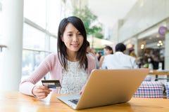 Mulher que usa o cartão de crédito para a compra em linha foto de stock