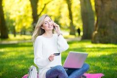 Mulher que usa o cartão de crédito que compra em linha com um portátil na paridade Fotografia de Stock Royalty Free