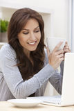 Mulher que usa o chá ou o café bebendo do computador portátil Fotografia de Stock Royalty Free