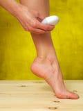 Mulher que usa o epilator em seus pés esculturais imagens de stock royalty free