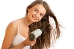 Mulher que usa o hairdryer Fotografia de Stock