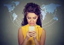 Mulher que usa o Internet conectado smartphone da consultação no mundo inteiro Fotos de Stock